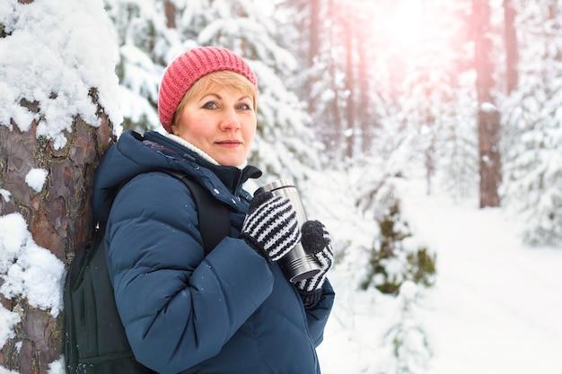 Heureuse femme qui marche dans la forêt d'hiver. une femme d'âge moyen gèle dans le parc.