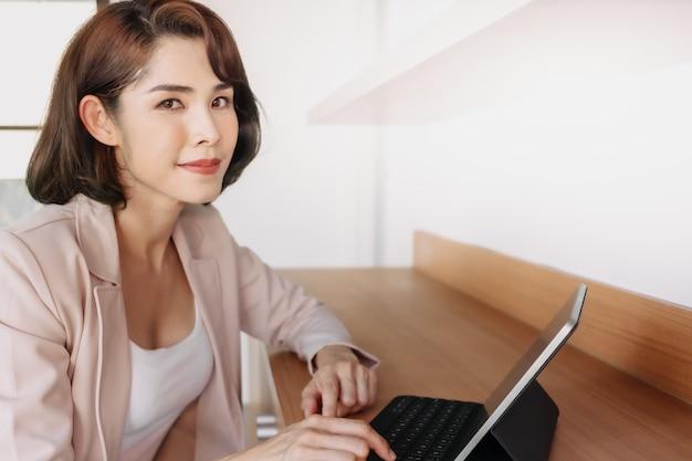 Heureuse femme qui travaille utilise une tablette au bureau