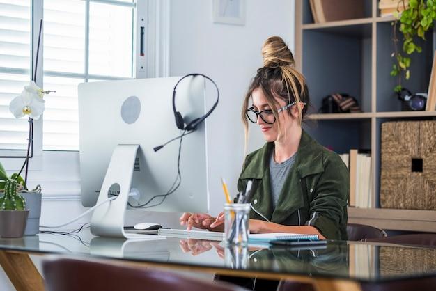 Heureuse femme de race blanche adulte en look professionnel à l'écran d'ordinateur portable fonctionne en ligne sur le gadget du bureau à domicile. souriante jeune femme utilise un ordinateur pour naviguer sur internet sur l'appareil. concept technologique.
