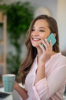 Heureuse femme ravie de répondre à l'appel téléphonique en se tenant debout avec une tasse de café