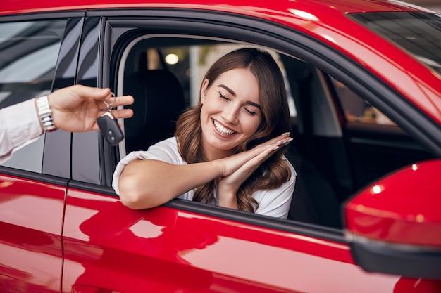 Heureuse femme recevant les clés de voiture du concessionnaire