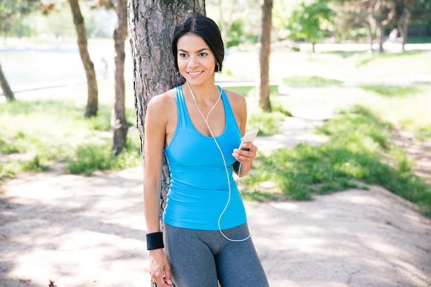 Heureuse femme réfléchie debout avec smartphone à l'extérieur