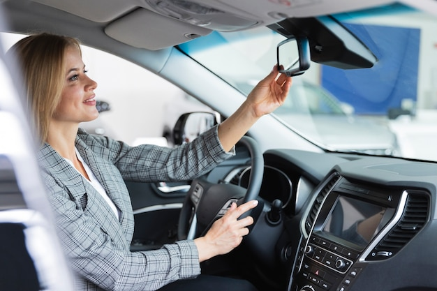 Heureuse femme regarde dans le rétroviseur de la voiture