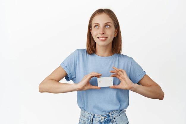 Heureuse femme rêveuse pensant acheter quelque chose, montrant une carte de crédit près de la poitrine et regardant de côté pensif, imagerie allant faire du shopping, mur blanc