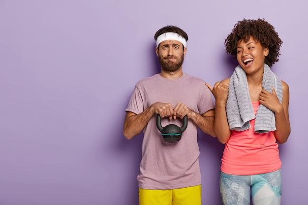 Heureuse femme rit sincèrement, pointe du doigt avec le pouce, indique au petit ami qui soulève du poids
