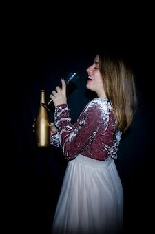Heureuse femme en robe buvant du champagne dans un verre