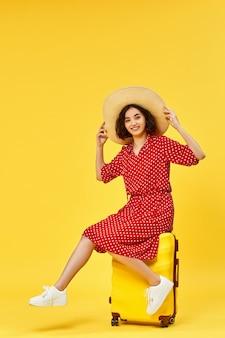 Heureuse femme en robe rouge avec valise va voyager sur fond jaune. concept de voyage.