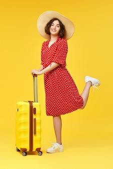 Heureuse femme en robe rouge avec valise va voyager sur fond jaune.