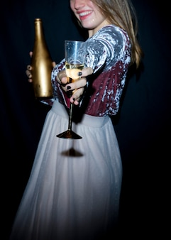 Heureuse femme en robe avec verre de champagne