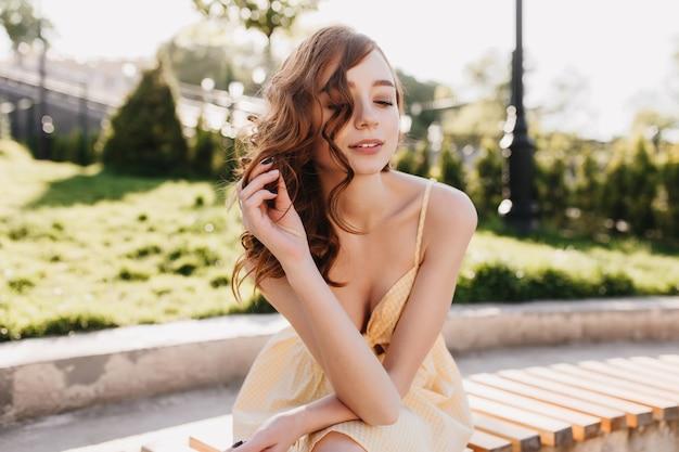 Heureuse femme romantique en robe jaune posant dans le parc. tir extérieur d'une dame au gingembre extatique profitant d'une chaude journée d'été.