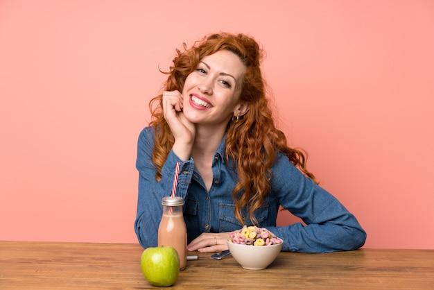 Heureuse femme rousse prenant son petit déjeuner