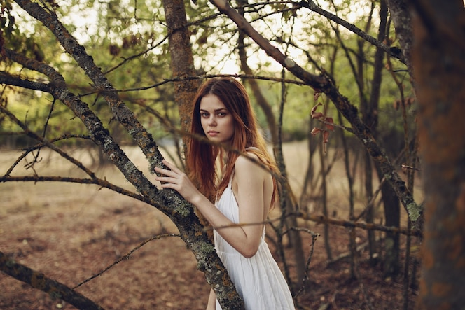 Heureuse femme rousse en robe blanche s'exécute sur l'herbe sèche dans la nature près des arbres