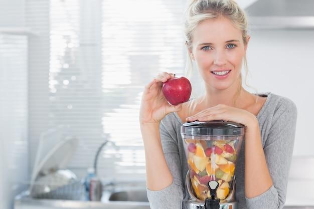 Heureuse femme s'appuyant sur son presse-fruits plein de fruits et tenant la pomme rouge