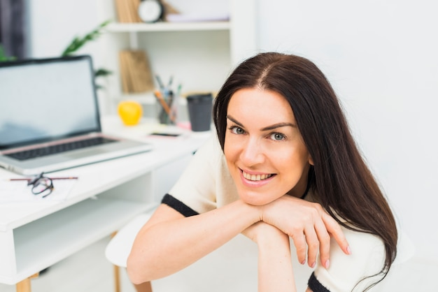 Heureuse femme se reposant sur une chaise au bureau
