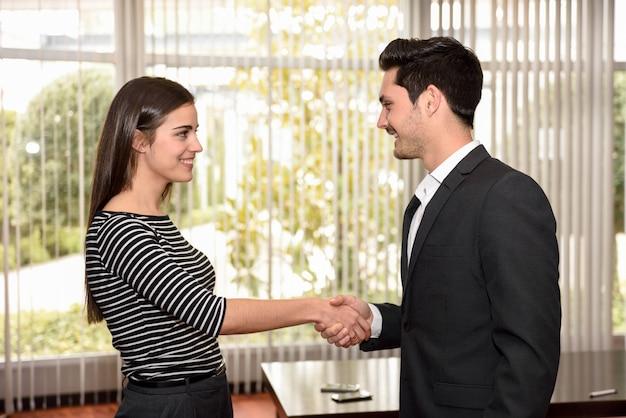 Heureuse femme se serrant la main avec son employeur après un entretien d'embauche