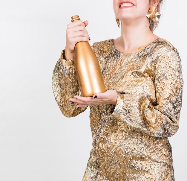 Heureuse femme secouant une bouteille de champagne