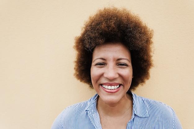 Heureuse femme senior africaine souriant à la caméra à l'extérieur dans la ville - focus sur le visage