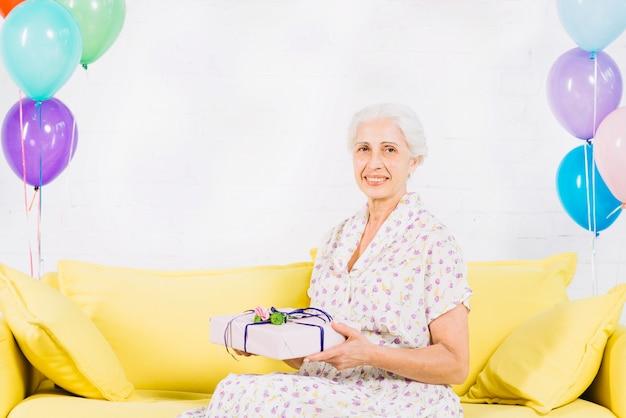 Heureuse femme senior assise sur un canapé avec un cadeau d'anniversaire