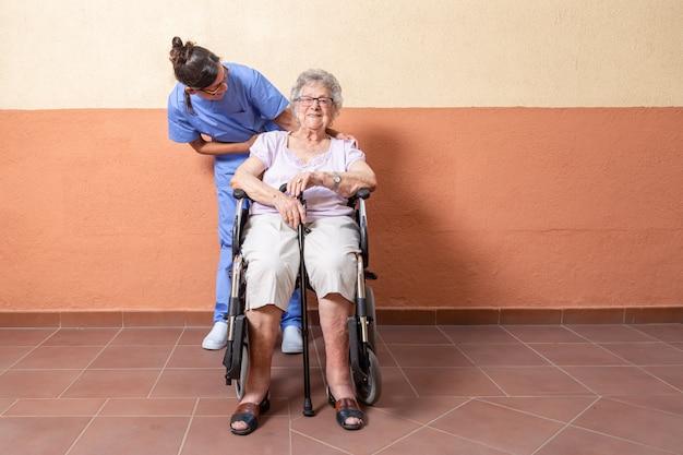 Heureuse femme senior avec bâton de marche en fauteuil roulant avec son soignant à la maison