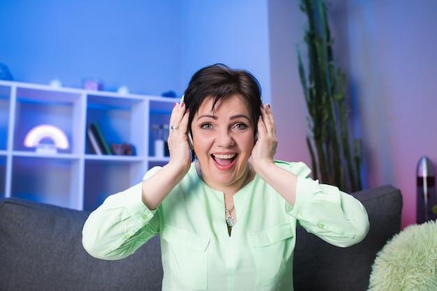 Heureuse femme senior dans les écouteurs, écouter de la musique à la maison. concept de technologie, de personnes et de style de vie. pensionné positif meloman chantant en musique. vie moderne et active après la retraite