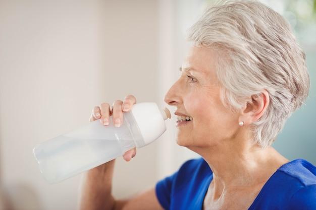 Heureuse femme senior l'eau potable après une séance d'entraînement