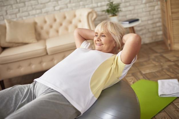 Heureuse femme senior faisant des exercices de pilates dans la chambre.