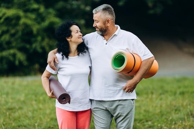 Heureuse femme senior et homme debout en plein air, tenant un tapis de yoga et se regardant mutuellement