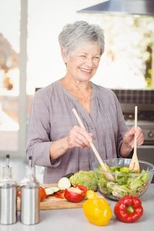 Heureuse femme senior jetant une salade debout dans la cuisine