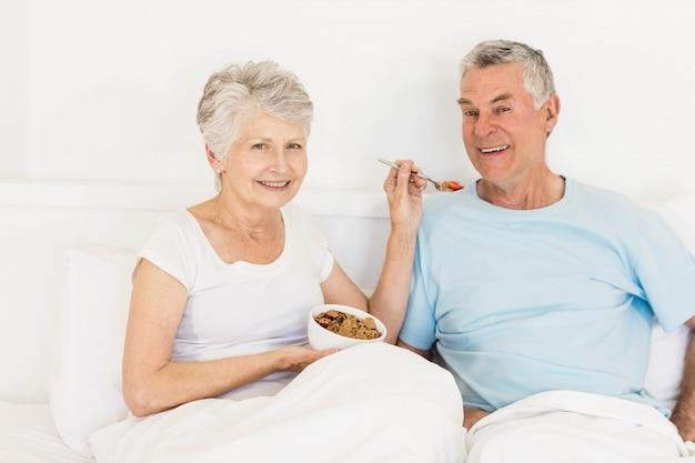 Heureuse femme senior nourrit son mari au lit