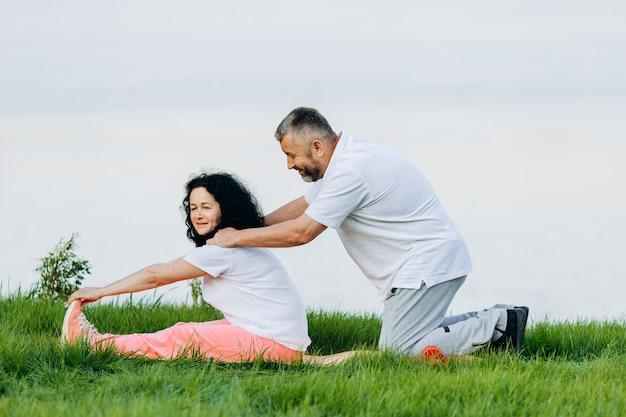 Heureuse femme senior prenant des exercices en plein air et homme faisant un massage pour elle