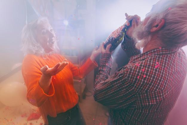 Heureuse femme senior regardant son mari en train de boire de l'alcool dans la chambre remplie de fumée