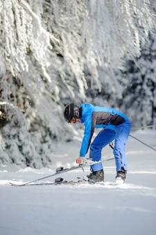Heureuse femme skieur sur une piste de ski dans la forêt