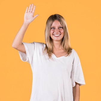 Heureuse femme sourde avec bras levé debout devant le fond uni