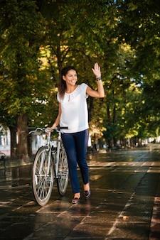 Heureuse femme souriante, agitant la main avec vélo au parc