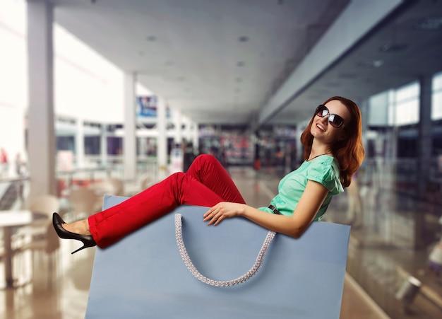 Heureuse femme souriante allongée dans le sac à provisions dans le centre commercial