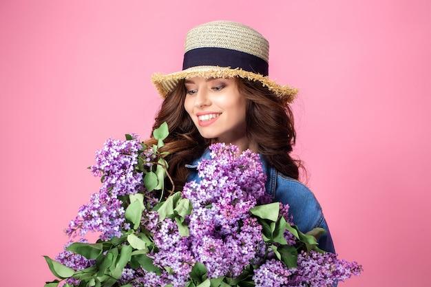 Heureuse femme souriante, appréciant l'odeur du bouquet de fleurs lilas sur