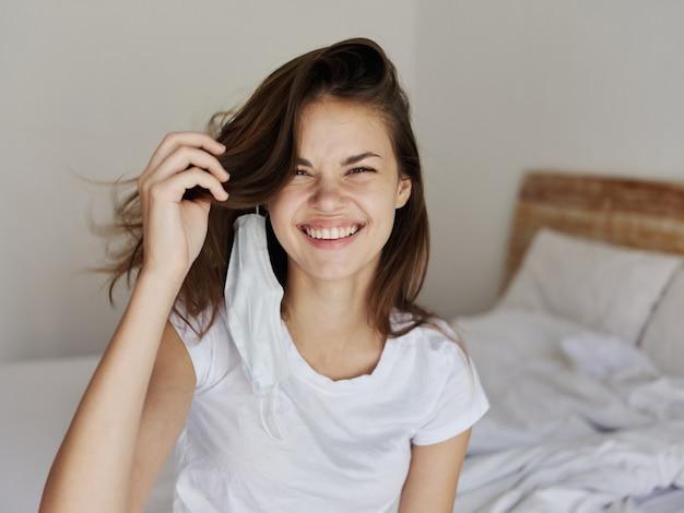Heureuse femme souriante et assise sur le lit masque médical à la main