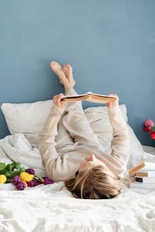 Heureuse femme souriante assise sur le lit en pyjama, avec plaisir en appréciant les fleurs et en lisant un livre
