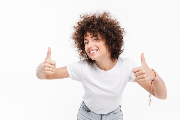 Heureuse femme souriante aux cheveux bouclés montrant deux pouces vers le haut
