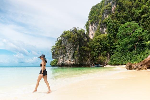 Heureuse femme souriante en bikini et chapeau de soleil marchant sur la plage.