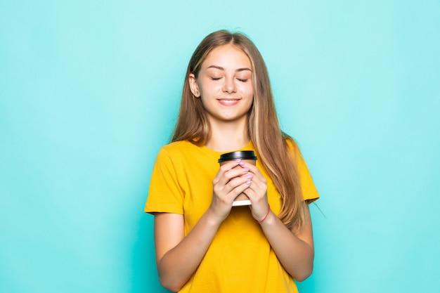 Heureuse femme souriante et boire du café isolé sur un mur turquoise