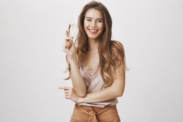 Heureuse femme souriante, boire du champagne à la fête