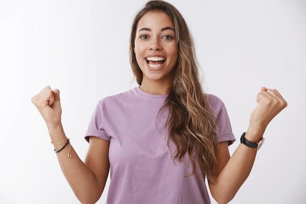 Heureuse femme souriante charmante excitée, cheveux bouclés bronzés, poings serrés célébrant joyeusement l'accomplissement, victoire réussie, hourra, victoire joyeuse, mur blanc amusé debout