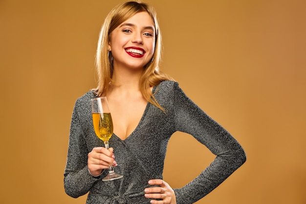 Heureuse femme souriante dans une robe glamour élégante avec un verre de champagne.