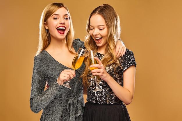 Heureuse femme souriante dans des robes glamour élégantes avec des verres de champagne sur le mur d'or