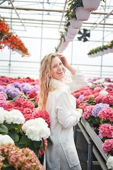 Heureuse femme souriante debout près de belles fleurs roses. serre industrielle avec hortensia coloré. jeune femme blonde dans une serre. fleurs en pots tout autour.