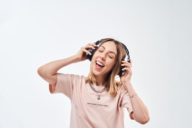 Heureuse femme souriante avec des écouteurs, écouter de la musique et danser
