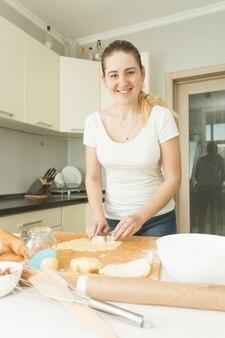 Heureuse femme souriante faisant de la pâte à biscuits sur un bureau en bois