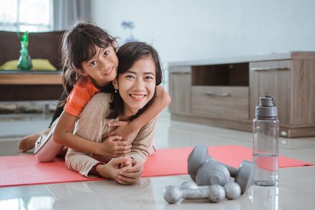 Heureuse femme souriante et fille regardant la caméra tout en exerçant ensemble à la maison