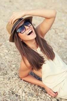 Heureuse femme souriante hipster au chapeau sur une plage